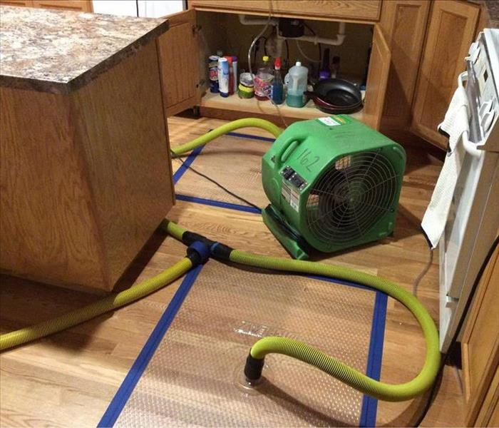A specialty mat system and an air mover drying out the wet hardwood flooring
