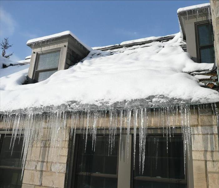 A snowy roof with ice crystals hanging off the gutters.