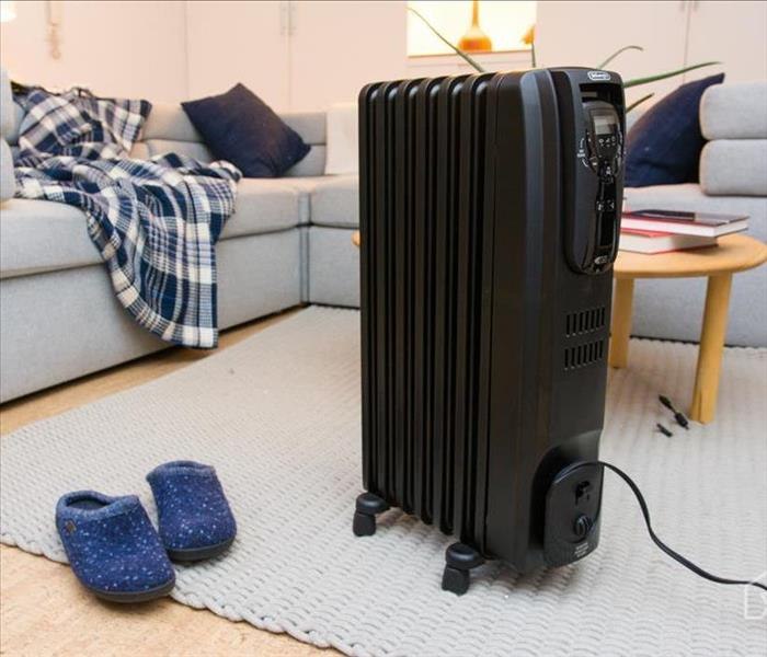 A Space heater sitting in the middle of the living room. There is a couch, slippers, and a coffee table sitting behind it.