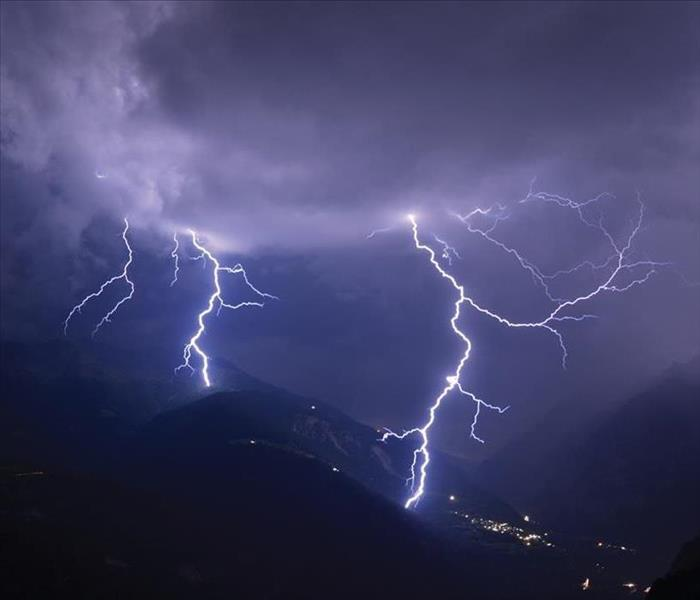 Mountains with streaks of lightning flowing across the sky